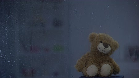 anlamı : Teddy bear on sill behind rainy window in thunder weather, hope and support