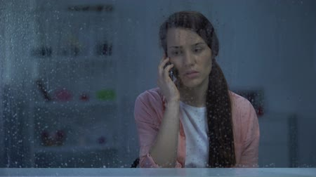 choque : Sad woman talking phone behind rainy window, shocked by bad news from family