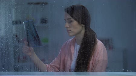 incurable : Frustrated woman looking on lungs x-ray on rainy day, incurable disease, cancer Stock Footage