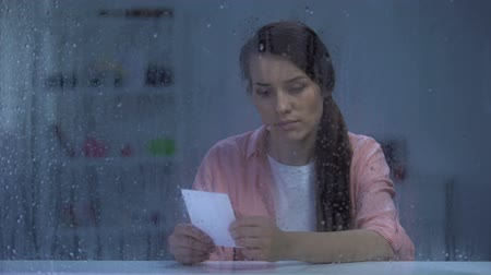 меланхолия : Upset woman looking at photo behind rainy window, missing husband after divorce