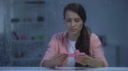 napětí : Upset woman holding pink socks of unborn child on rainy day, infertility problem