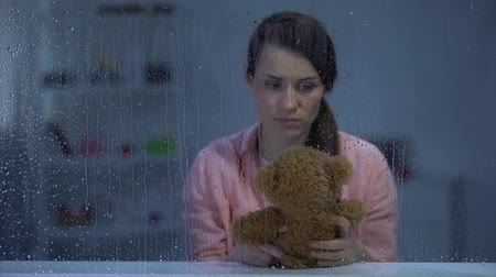 без вести пропавшие : Hopeless middle-aged woman holding teddy bear, looking for support, rainy day