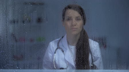 üzgün : Upset female doctor looking through rainy window, work problems, close-up Stok Video