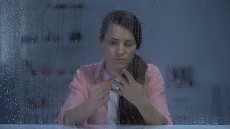без вести пропавшие : Woman taking off engagement ring behind rainy window, upset after break up