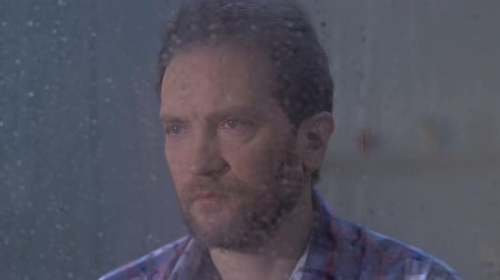 adam : Depressed middle-aged male looking in rainy window and thinking, loneliness