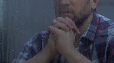 лучше : Middle-aged male praying god behind rainy window, hoping for better.