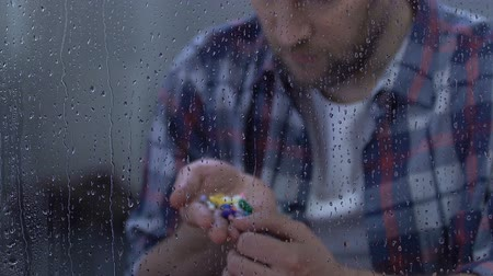 incurable : Depressed sick man holding full palm of medication, sitting behind rainy window Stock Footage