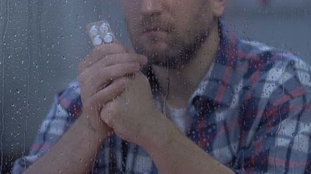 incurable : Male holding tablets and looking to rainy window, drug side effect, disease