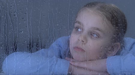меланхолия : Sad girl looking in window on rain drops, dreaming about family in orphanage Стоковые видеозаписи