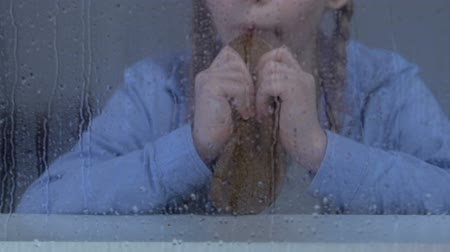 tehetetlen : Poor girl eating bread behind rainy window, insecure social layer, orphanage