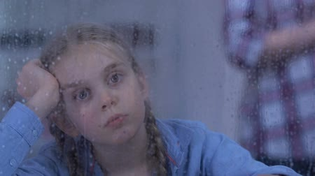 coming home : Sad orphan girl looking at rain, couple standing behind, foster family coming