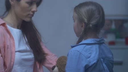 плюшевый мишка : Mother comforting little sad daughter holding teddy bear, parental support, care
