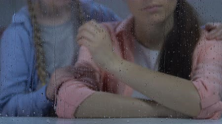 把握 : Little girl comforting mother sitting near rainy window, depressed after divorce 動画素材