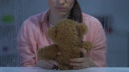 remembering : Distressed lady holding teddy bear, missing gone child and suffering depression