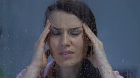 sensibilidad : Lady suffering strong headache, massaging temples and looking in rainy window