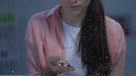 ümitsizlik : Sad lonely unhealthy woman holding palm of medication, sitting near rainy window Stok Video