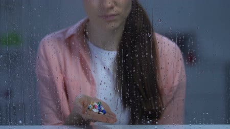 incurable : Lonely sick woman holding palm of medication near rainy window looking to camera
