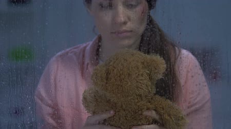 mistreatment : Sad female with wound on cheek hugging teddy bear, remembering happy childhood