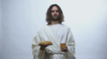 communion : Jesus holding wine and bread on illuminated background, Christian ceremony