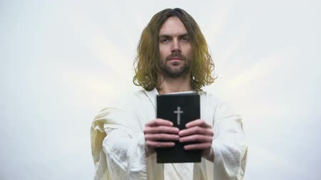 holy book : Jesus giving Holy Bible, calling for prayer, righteous living in catholicism