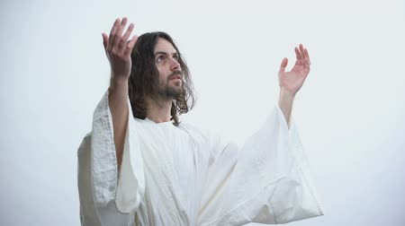 acreditar : Saint man in robe raising hands to light, praying to God, religious conversion