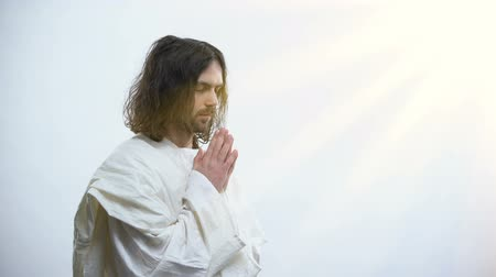 благодать : Religious man praying to God, light falling as sign of forgiveness, God mercy Стоковые видеозаписи