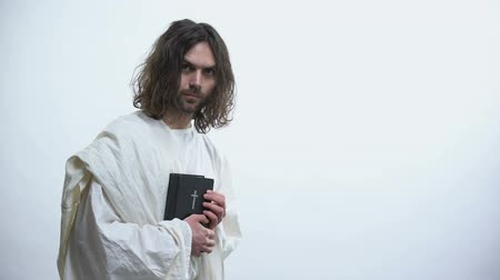 megváltás : Jesus showing Holy Bible to camera, calling for prayer, Christian teachings