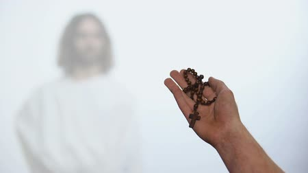 požehnat : Male hands holding Rosary, praying to appeared God on background, salvation