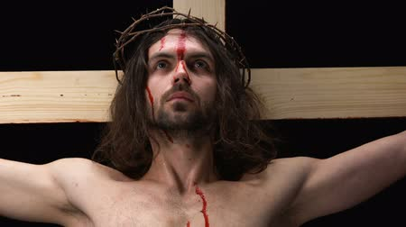 megmentő : Crying son of God in thorns crown suffering on wooden cross, symbol of faith Stock mozgókép