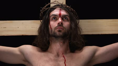 chrześcijaństwo : Bleeding savior in crown of thorns on black background suffering on cross, pray