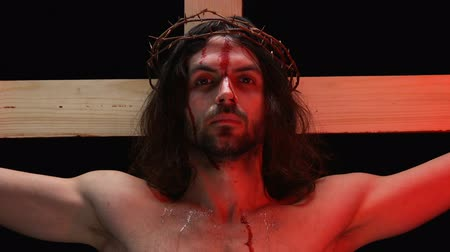 crucified : Jesus Christ suffering agony in red lights, blood and tears on body, crucifixion Stock Footage