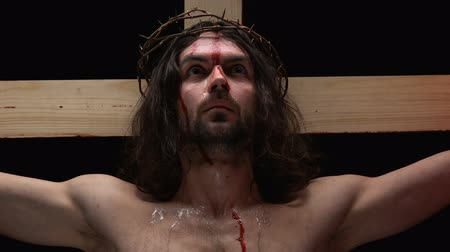 forever : Sacrificing messiah in crown of thorns looking camera, tears and blood on body