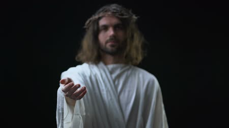 jewish people : Son of God in crown of thorns stretching out hand on dark background, mercy
