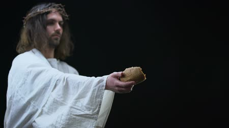 fiel : Jesus giving bread to poor man on black background, biblical history, support Stock Footage