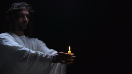 fiel : Male covering Jesus hands holding burning light, religious hope, faith symbol Stock Footage