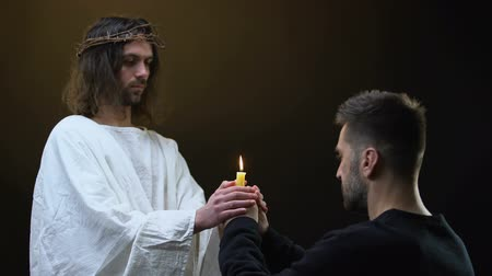 acreditar : Male parishioner and Jesus praying holding burning candle together, faith symbol