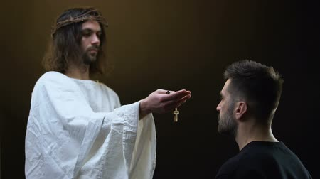 holy scripture : Jesus in crown of thorns giving wooden cross necklace to praying man, hope Stock Footage