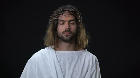 holy scripture : Suffering son of God closing eyes on dark background, faith in miracle, spirit Stock Footage