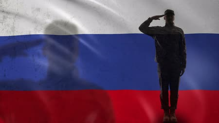 peacekeeping : Russian soldier silhouette saluting against national flag, country defense