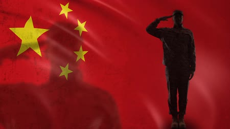 peacekeeping : Chinese soldier silhouette saluting against national flag, army rocket force Stock Footage