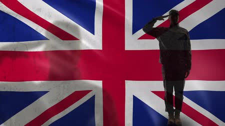 герои : British soldier silhouette saluting against national flag, independence day