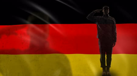 peacekeeping : German soldier silhouette saluting against national flag, memorial day, defense