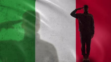 peacekeeping : Italian soldier silhouette saluting against national flag, proud army officer