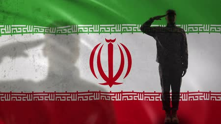 veterano : Iranian soldier silhouette saluting against national flag, military veteran