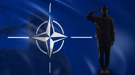 gurur : BRUSSELS, BELGIUM - CIRCA APRIL 2019: NATO flag with saluting soldier silhouette, collective defense of territory Stok Video