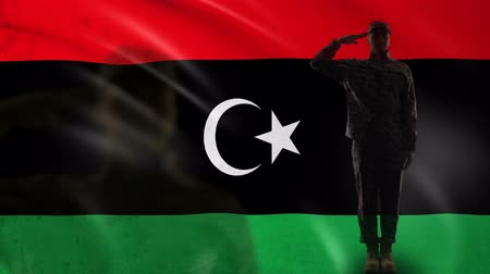 peacekeeping : Libya soldier silhouette saluting against national flag, military occupation Stock Footage