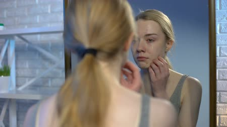 insecurities : Depressed young woman looking at puberty pimples on face in mirror reflection