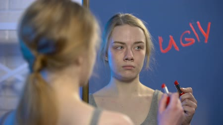 dermatologia : Unhappy teenager writing word ugly by lipstick on mirror, puberty insecurities Stock Footage