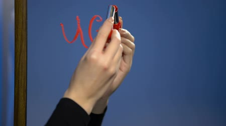 criticism : Woman hand writing word ugly by red lipstick mirror glass, young age criticism Stock Footage