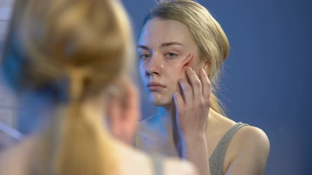 batido : Sad female victim looking at face wound in mirror, domestic violence, abuse Stock Footage